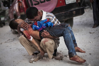 A Syrian man cries while holding the body of his son near Dar El Shifa hospital in Aleppo, Syria, Oct. 3, 2012. The boy was killed by the Syrian army. Photo by Manu Brabo